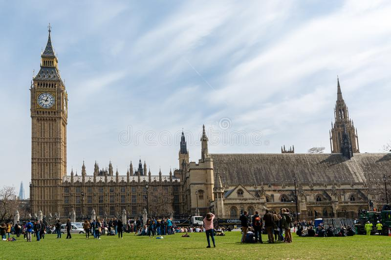 London, England; 03/12/2016: Houses of parliament and big ben in london. British Parliament and the famous Big Ben clock from a garden full of tourists and a royalty free stock photos