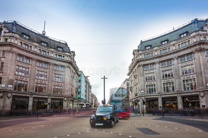 London, England - Iconic black taxi and red double decker bus at the famous Oxford Circus with Oxford Street and Regent Street royalty free stock image