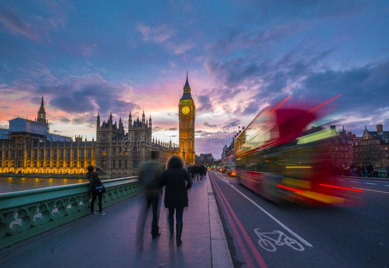 London, England - Iconic Red Double Decker Bus on the move on Westminster Bridge with Big Ben and Houses of Parliament. At background. Sunset with beautiful royalty free stock photo