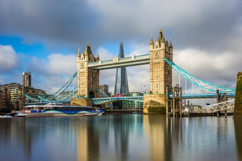 London, England - Iconic Tower Bridge at sunrise with sightseeing boat and red double-decker bus stock photography