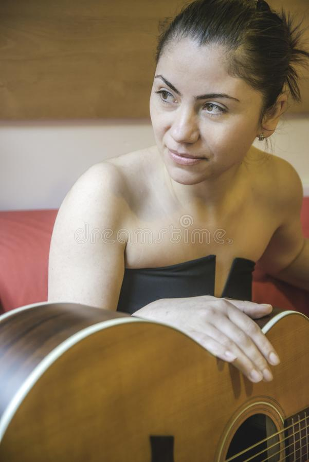 London,England,January 22,2015. Young woman during a guitar lesson royalty free stock images