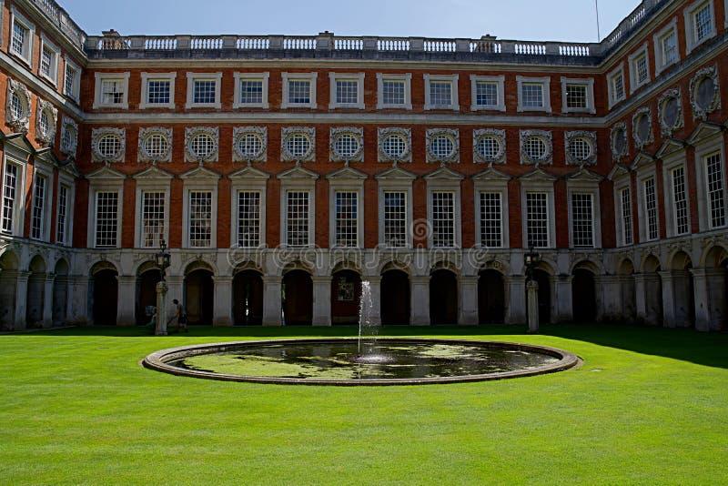 London England, Juli 16th 2019: Sikt av den Hampton Court Palace borggården med blå himmel royaltyfri foto