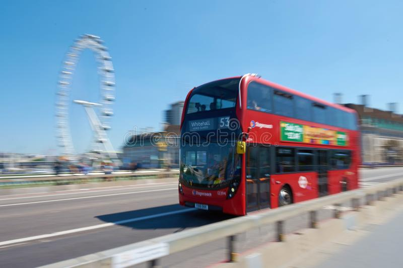 LONDON / ENGLAND - June 26, 2018 : Red double-decker bus is driving along the Westminster Bridge and Coca-Cola London Eye on back. Ground stock images