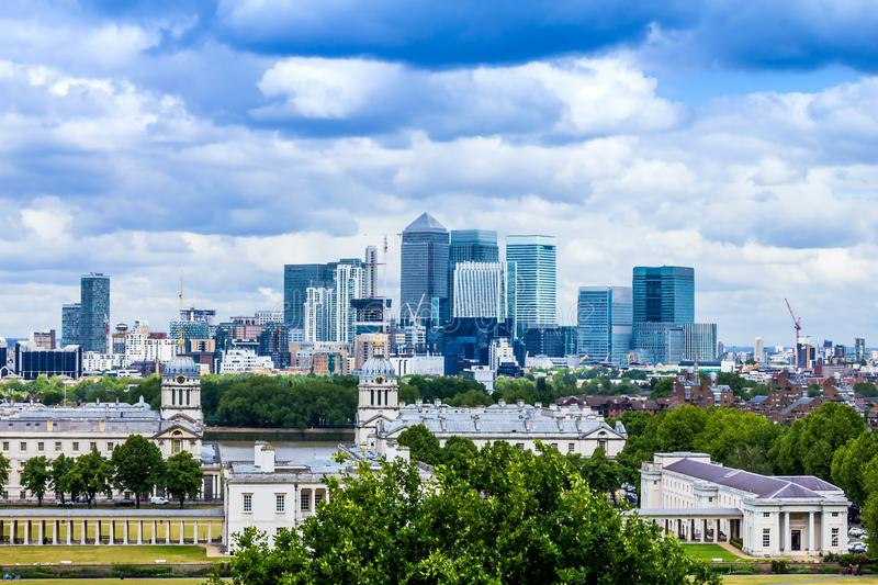 Skyline view of the skyscrapers of Canary Wharf and national maritime museum, shot from Greenwich park at sunset - London, UK royalty free stock photos