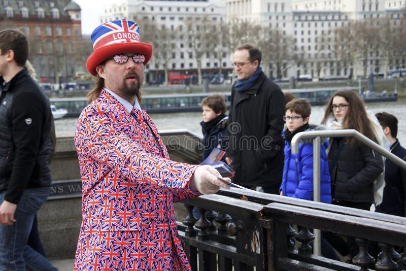 London, England: Am 8. März 2018: Ein Mann gekleidet in der britischer Flaggenjacke und -Sonnenbrille und ein ` London-` Hut, der lizenzfreie stockfotografie