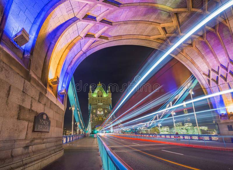London, England - Night shot of the world famous colorful Tower Bridge in London with double decker bus light trails stock images