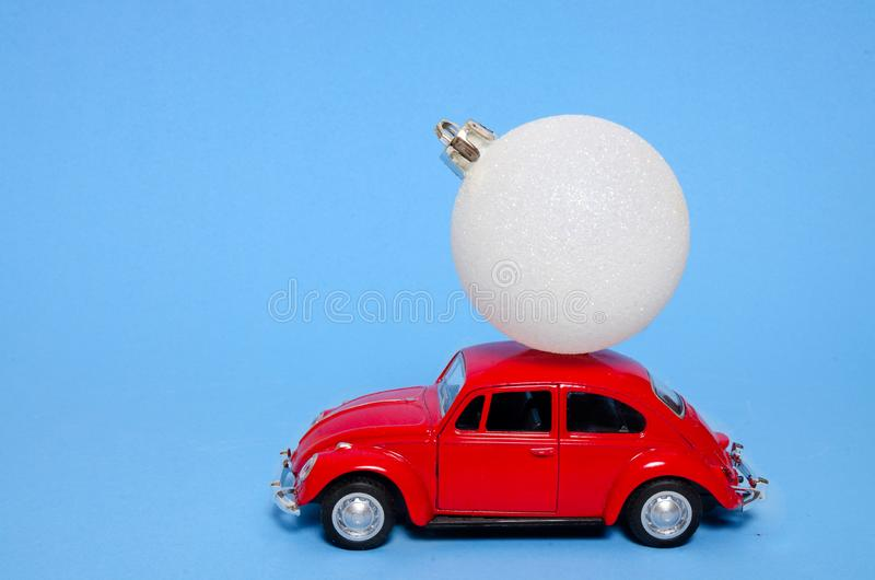 London, England - November 17 2019: red toy car and snow ball on the roof on the blue background. Red vintage toy car with. Christmas tree decoration snow ball royalty free stock image