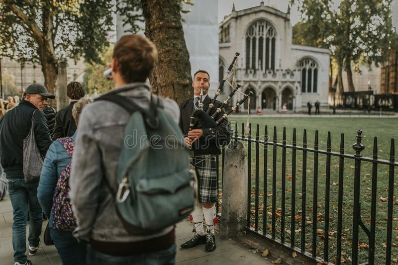 Bagpiper playing pipe at Westminster Abbey entrance, while tourist walk around by the sidewalk. royalty free stock photo