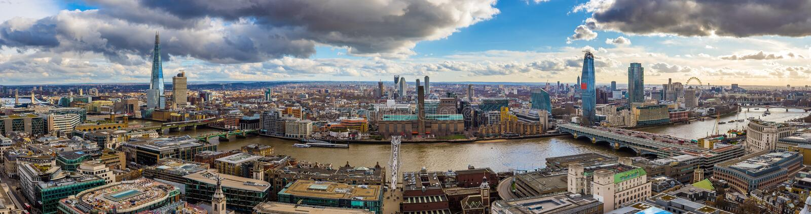 London, England - Panoramic skyline view of London with Millennium Bridge, famous skyscrapers and other landmarks. With beautiful blue sky and clouds royalty free stock images
