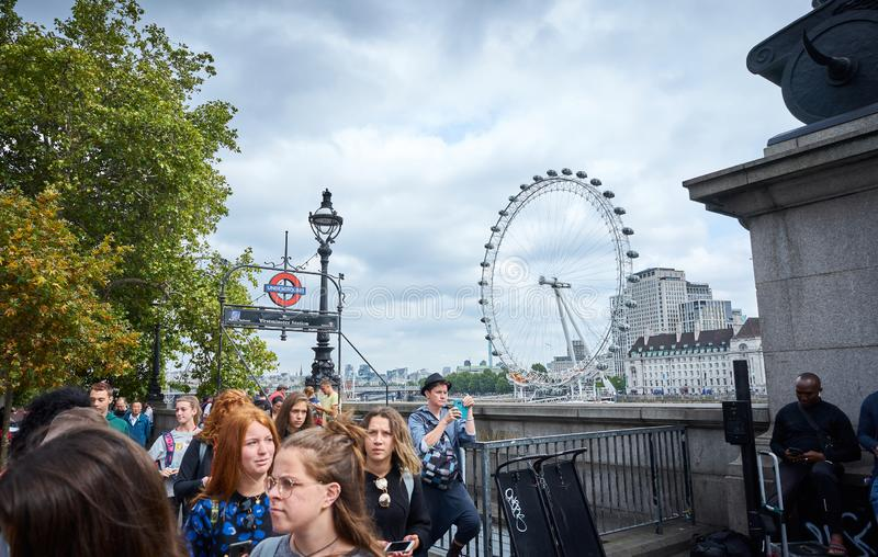 LONDON England - 08/21/2019: people leaving London`s Westminster underground station overlooking the ferris wheel stock photos