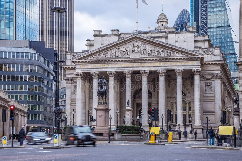 London, England - The Royal Exchange building with moving traditional black london taxi stock images