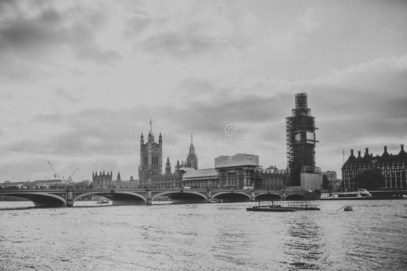 Black and white cityscape of Thames River and City of Westminster, with vintage style, with sun and clouds in the sky, in London, stock photos