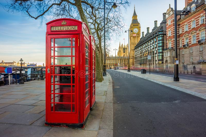 London, England - Traditional Old British red telephone box at Victoria Embankment with Big Ben. At background stock images