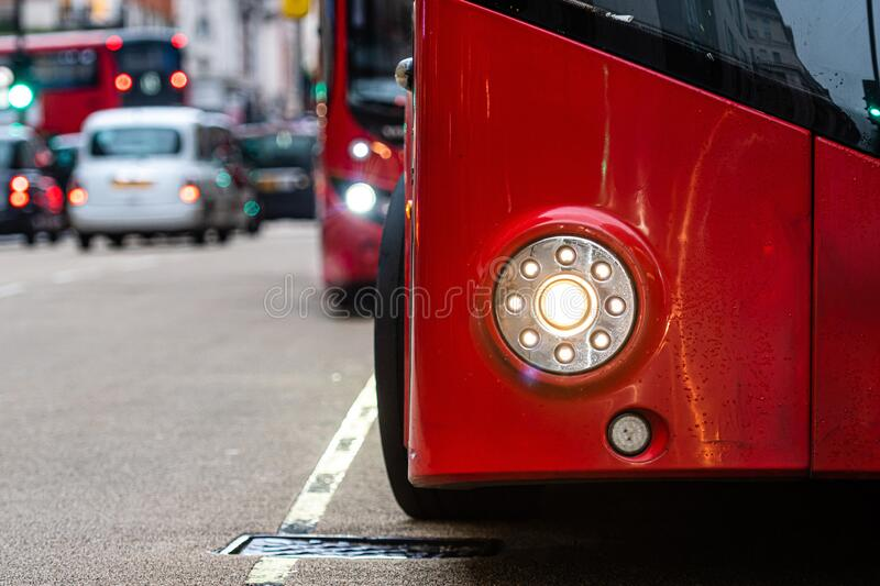 London, England, UK - December 31, 2019: Close-up of a red double decker bus headlight on a defocused city street background. Image stock photography