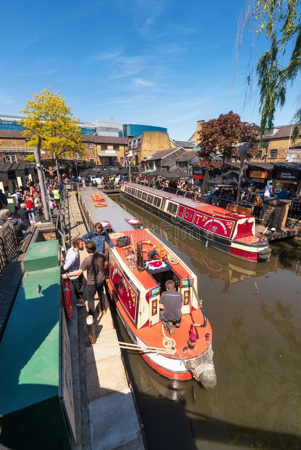 London, England UK - May 14, 2019: Boat navigating to the Regent`s Canal with people around in Camden Lock or Camden royalty free stock photos