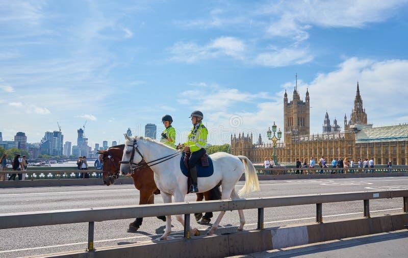 London, England - 08/21/2019: Zwei Polizisten reiten auf Pferd über die Westminster-Brücke von London, die das Parlament überblic lizenzfreie stockfotos