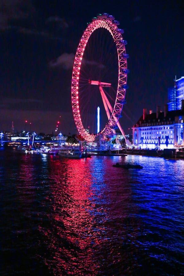 London Eye en la noche con la reflexión del agua fotos de archivo