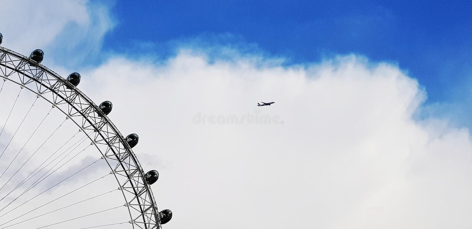 London eye. Ferris, ferriswheel, flight, plane, aeroplane, sky, clouds, blue, bluesky, nature, natural, scenic, beautiful, awesome, shot, time, timi, timing royalty free stock photography