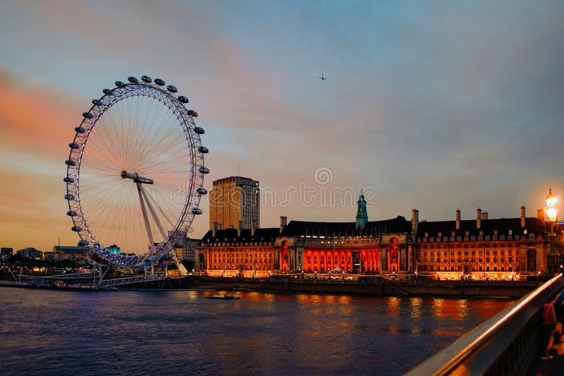 London Eye Ferris Wheel and County Hall in London dusk stock photography