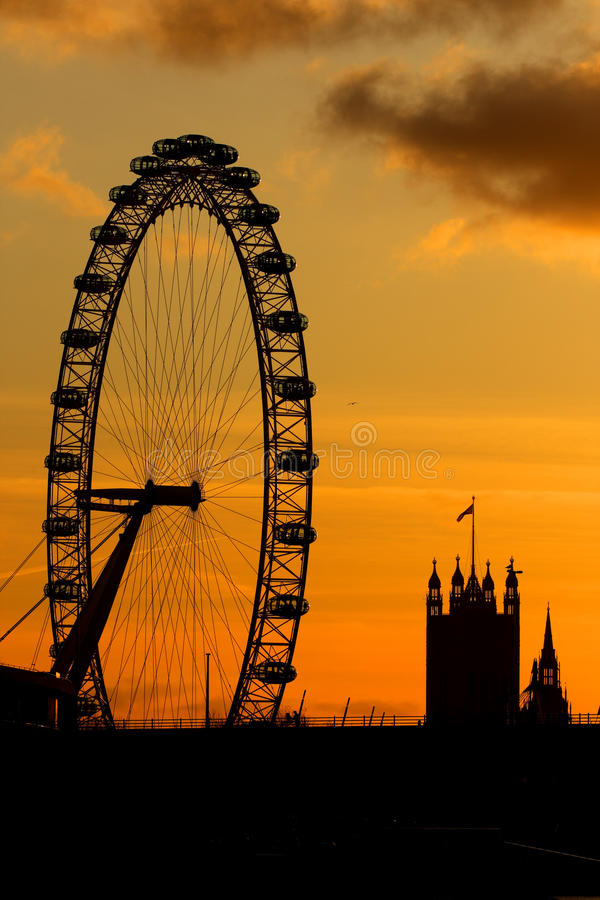 London Eye in London. A sunset view of the London Eye wheel with the Houses of Parliement Tower in the horizon royalty free stock image