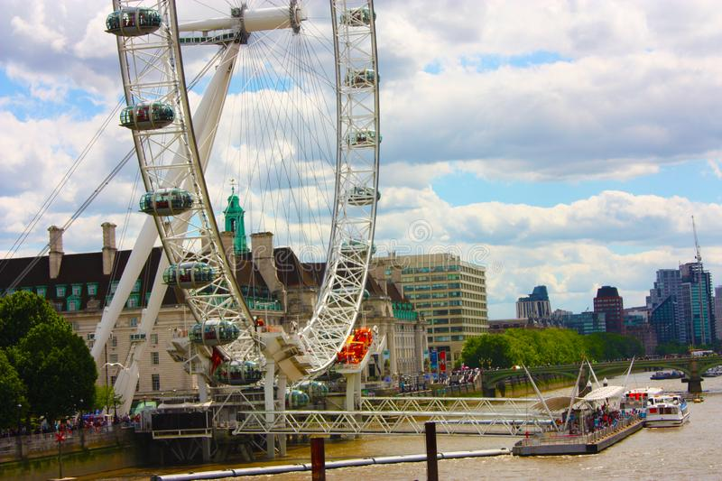 The london eye on the river under a gray and cloudy spring sky royalty free stock photo