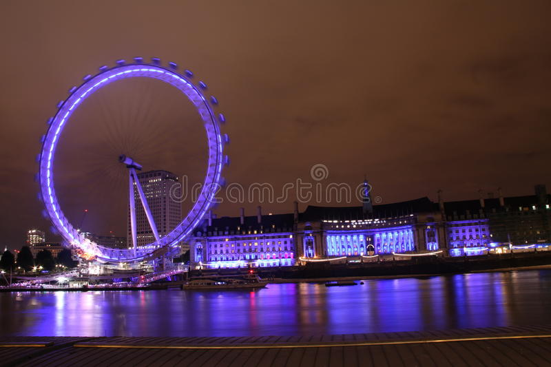 The London Eye and Southbank at night. The London Eye wheel and buildings on the Southbank illuminate the River Thames with a purple glow at night royalty free stock photos