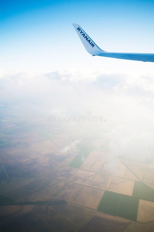 LONDON FÖRENADE KUNGARIKET - April 12, 2015: Ryanair logo på flygplans vinge i mitt--luft över Förenade kungariket royaltyfri foto