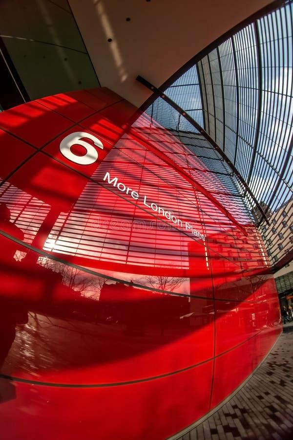 London Förenade kungariket - Februari 10, 2007: Extremt brett fisheyefoto, röd vägg av 6 mer London ställebyggnad som förbi planl royaltyfri foto