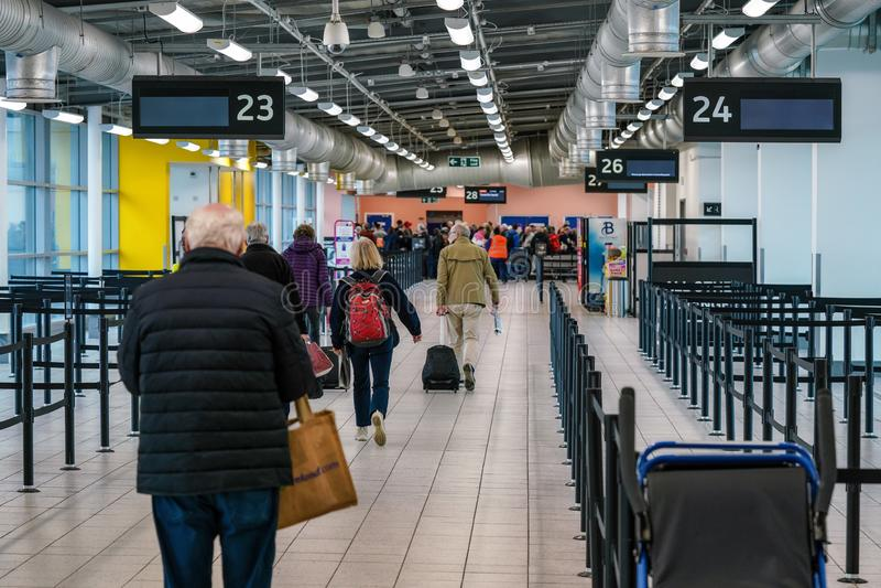 London, Förenade kungariket - februari 2019: Passagerare som går i avgångshallen för att ta sig till skrivbordet för sin flygning royaltyfri foto