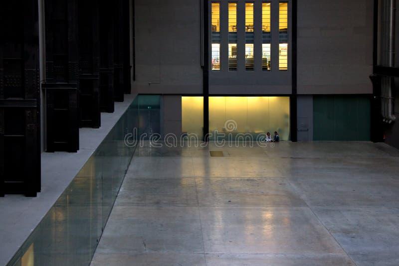 London Förenade kungariket - mars 17, 2007: Okända par som sitter på golv av Tate den moderna huvudsakliga korridoren Konstgaller royaltyfria foton