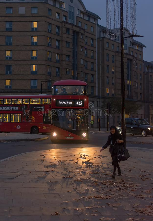 LONDON FÖRENADE KUNGARIKET - NOVEMBER 24, 2018: Den traditionella London röda bussen passerar nattgenomskärningen royaltyfri fotografi