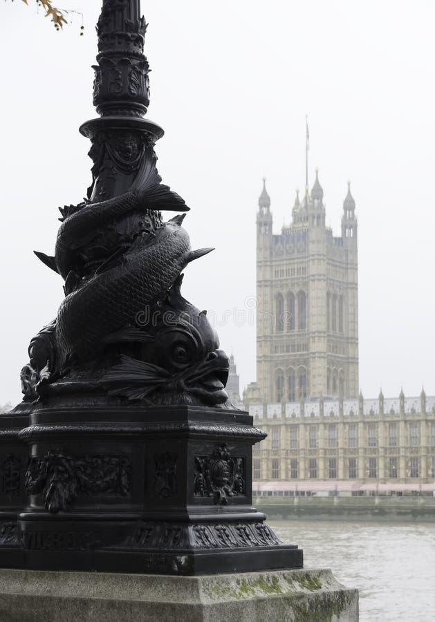 LONDON FÖRENADE KUNGARIKET - NOVEMBER 23, 2018: Dimmigt Sikt av Themsen och husen av parlamentet Forntida Streetlight royaltyfri foto