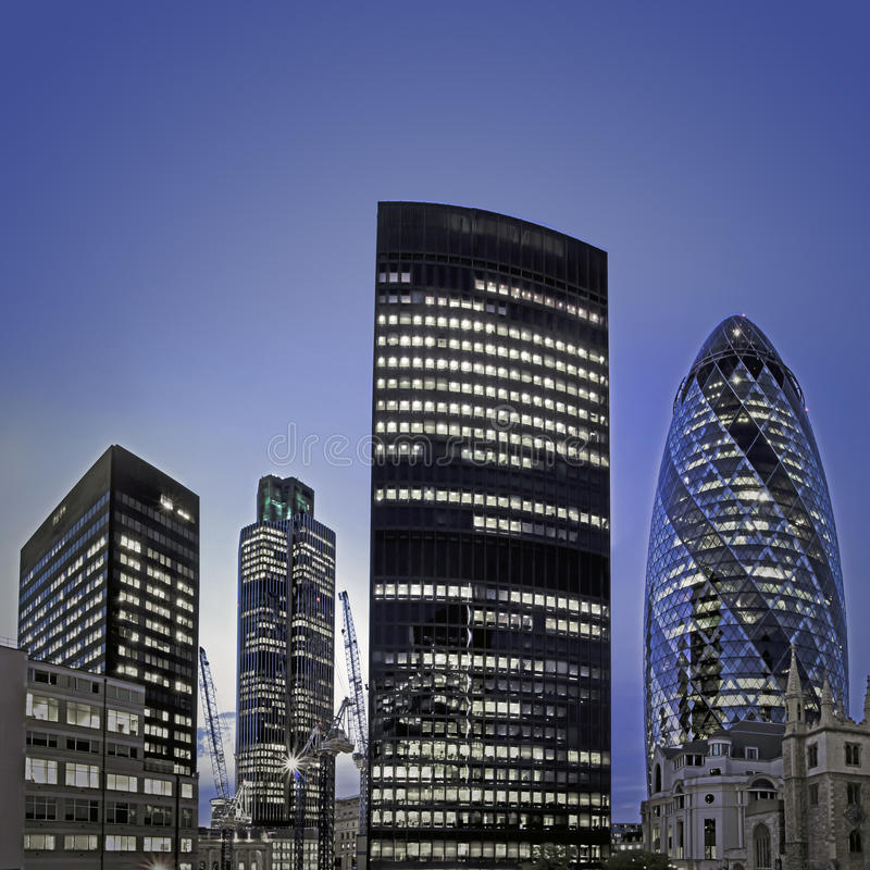 London financial district at twilight. Evening time shot of London's famous skyscrapers including 'the Gherkin', Aviva and Tower 42 in the heart of it's stock image