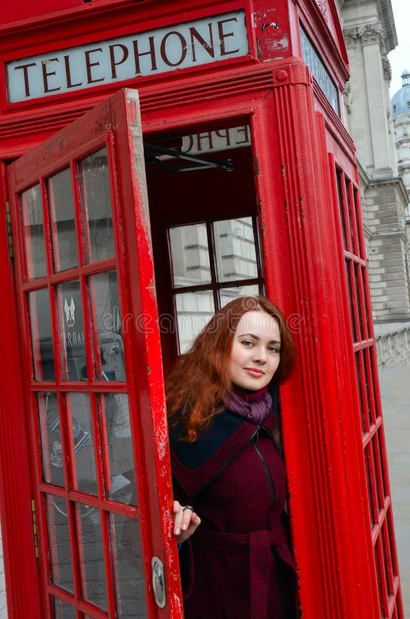 London girl. Young woman by red phone booth. Portrait of beautiful smiling happy young woman standing in London royalty free stock image