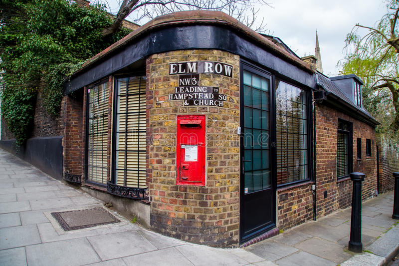 LONDON, Großbritannien - April, 13: Roter Postbox mit mit Ziegeln gedecktem Straßenschild, London lizenzfreie stockfotografie
