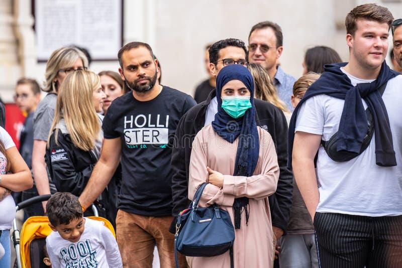 London, Großbritannien, am 28. Juli 2019 Leute-aufpassende Straßen-Leistung Verschmutzungs-Gesichtsmaske der jungen Asiatin trage stockbilder