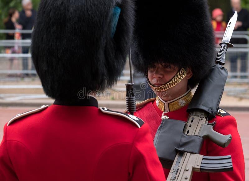 London Großbritannien Zwei königliche Schutzsoldaten in den Rot- und Schwarzes Uniform- und Bearskinshüten, die einen freundliche stockfotografie