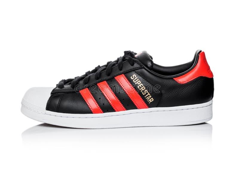 LONDON, GROSSBRITANNIEN - 5. JUNI 2019: Adidas-Vorlagen-Superstarschwarzschuh mit roten Streifen auf weißem Hintergrund Deutsches lizenzfreie stockbilder