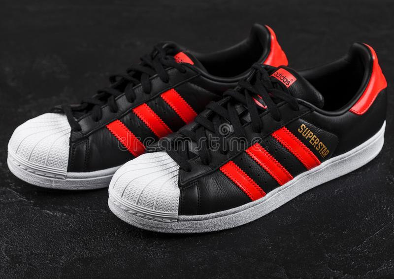 LONDON, GROSSBRITANNIEN - 5. JUNI 2019: Adidas-Vorlagen-Superstarschwarzschuhe mit roten Streifen auf schwarzem Hintergrund Deuts lizenzfreie stockfotos