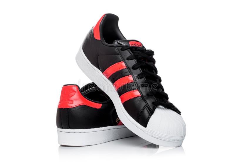 LONDON, GROSSBRITANNIEN - 5. JUNI 2019: Adidas-Vorlagen-Superstarschwarzschuhe mit roten Streifen auf weißem Hintergrund Deutsche lizenzfreie stockfotos