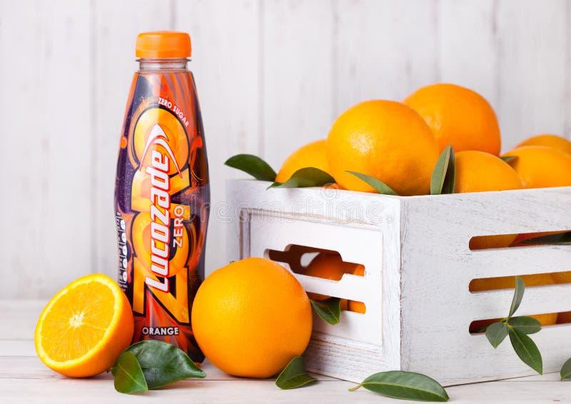 LONDON, GROSSBRITANNIEN - 31. MÄRZ 2018: Plastikflasche des alkoholfreien Getränkes Lucozade-Orange null mit frischen rohen Orang stockfotografie