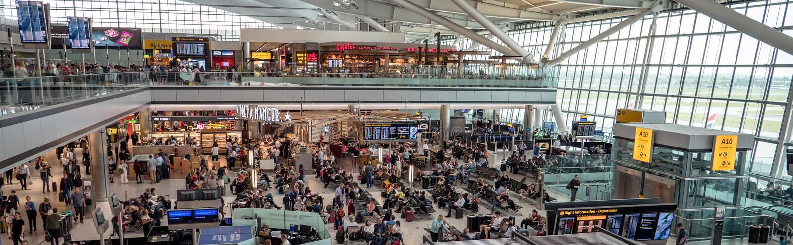 Panoramic London Heathrow Airport terminal 5 departure hall restaurants, shops and cafes. Passengers waiting to board flights. London Heathrow Airport T5, United royalty free stock photo