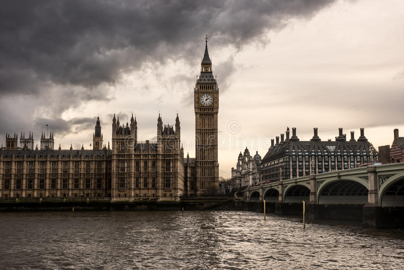 London, UK - The Houses of Parliament, the Big Ben and Westminster Bridge under dark clouds royalty free stock images