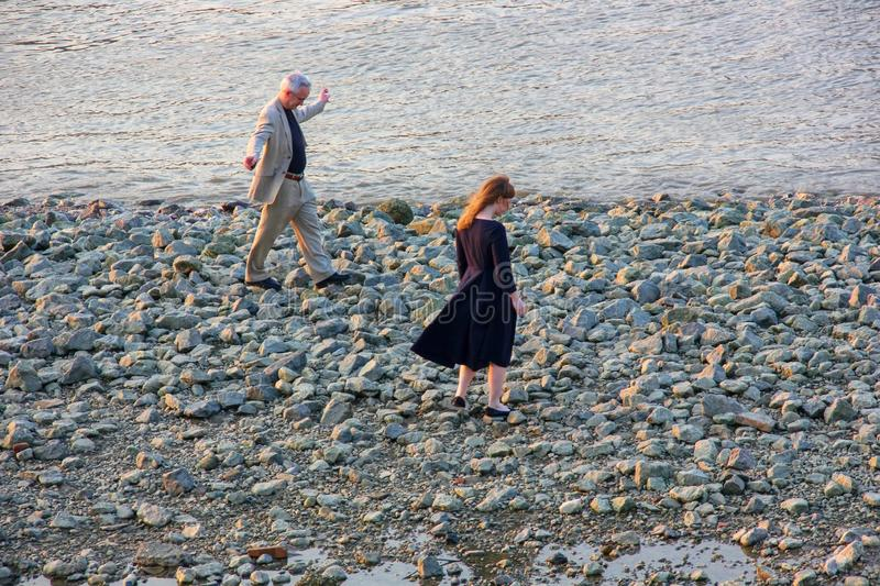 An elderly man  with his granddaughter, a student are joyful walking on the rocky bank of the Thames in the evening royalty free stock photography