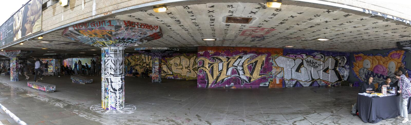 Southbank Skate Park in London. London - July 29, 2017: A panoramic photo of the Southbank Skatepark undercroft, comprised of ledges, banks and stairs covered royalty free stock photography