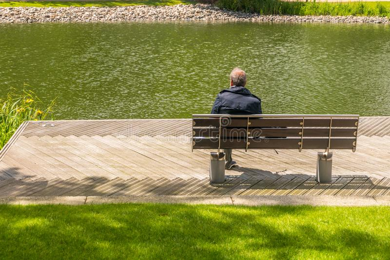 Alone man sits leg over on bench beside the swamp,  Men relax and watch the water in the marsh stock images