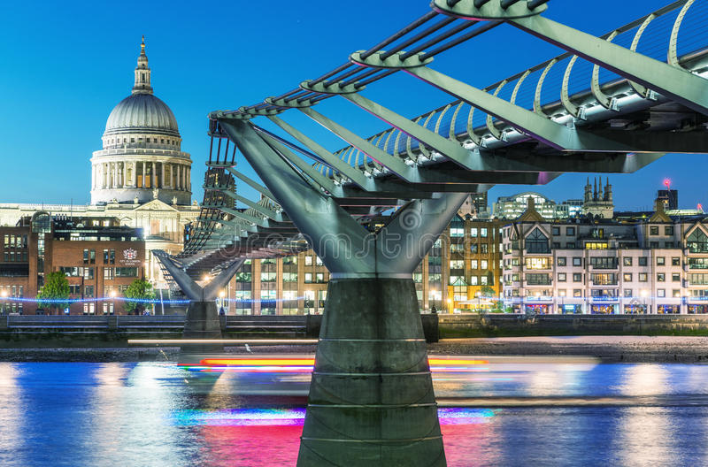 LONDON - JUNE 15, 2015: City night skyline with St Paul Cathedral and Millennium Bridge. London attracts 50 million people annual royalty free stock images