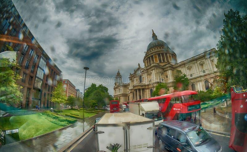 LONDON - JUNI 2015: Röda bussar near St Paul Cathedral på ett regnigt royaltyfri fotografi