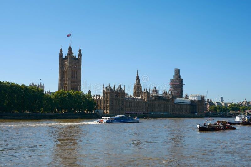 LONDON - Juni 25, 2018: Sikt av den London parlamentet med Big Ben i material till byggnadsställning ovanför Thameset River royaltyfri fotografi