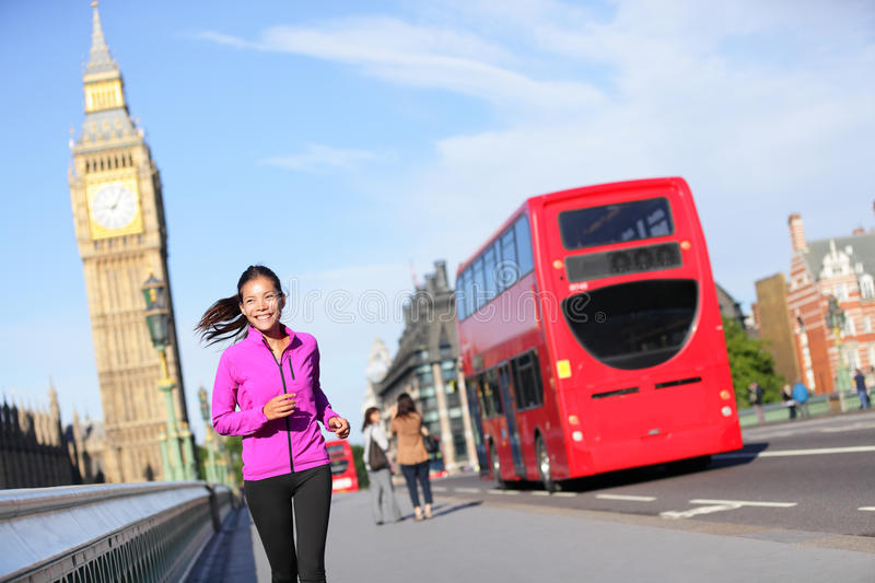 London lifestyle woman running near Big Ben. Female runner jogging training in city with red double decker bus. Fitness girl smiling happy on Westminster royalty free stock photo